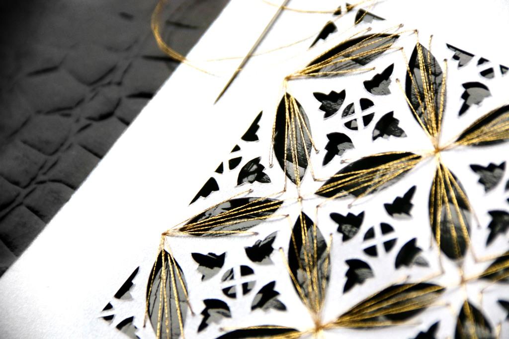 Paper cutting motif tradisional Indonesia dengan tingkat kerumitan tinggi, dipotong dengan cutter di kertas, dijahit dengan benang emas